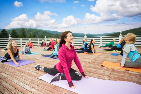 Relaxed and happy woman smiling and practicing yoga with group of girls. Beautiful slender woman smiling and doing half pigeon asana during class. People sitting on yoga mats.