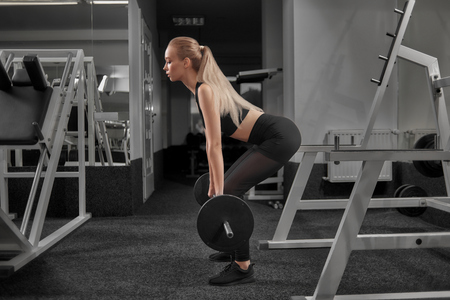 Beautiful fit woman has healthy and strong body. Active, athletic girl holding barbell, doing squats in modern gym. Sportswoman with ponytail wearing in black sneakers sportswear.