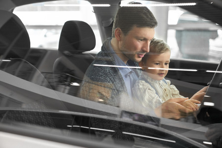 View from side window, father and son sitting inside of automobile. Parent and child sitting in car cabin, in drivers seat looking at steering wheel. Potential buyer testing vehicle. Stock Photo