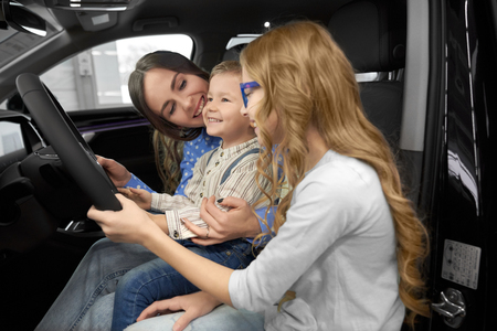 Mother sitting with children in car cabin of new automobile, observing and testing auto. Woman holding cute, happy son on knees, beautiful daughter holding hand on steering wheel.