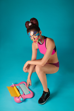 Beautiful model wearing in pink sportive top, has coroful pop art make up and bow hairstyle. Funky girl looking at camera, posing in squatting pose. Pink and blue toy typewriter.