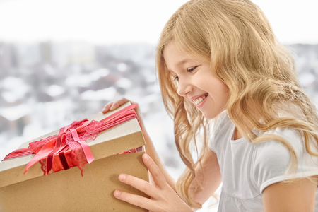 Beautiful girl with long, blonde, curly hair smiling and opening big craft box with red bow. Happy daughter receiving present on holiday and rejoicing. Teenager celebrating birthday.