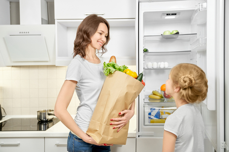 Mother standing in modern kitchen, holding big paper bag with vegetables, greens and baguette. Daughter standing near empty fridge. Fresh products after shopping.