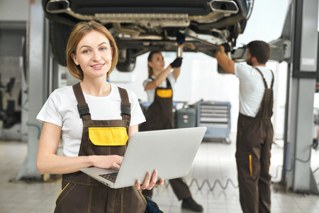 Beautiful young woman, worker of autoservice posing, holding laptop in hands. Pretty girl looking at camera, smiling. Mechanics fixing, repairing automobile lifted on bridge behind.