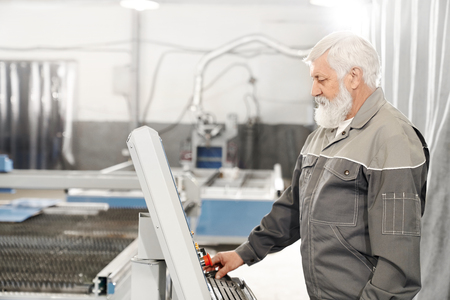 Edlerly bearded man operating laser plasma cutter on metalworking factory. Experienced engineer wearing in grey uniform working with computerized machine. Reklamní fotografie