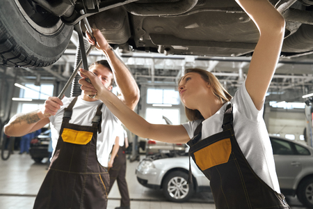 Concentrated young woman and man repairing auto in autoservice station. Professional female and male mechanics holding tools, wrenches and fixing undercarriage of vehicle. 版權商用圖片
