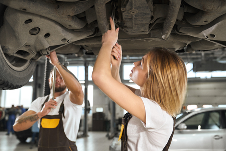 Mechanics wearing in white t shirts and coveralls. Workers using tools, wrenches for fixing vehicle in autoservice. Young woman and man working together with undercarriage of automobile. 版權商用圖片