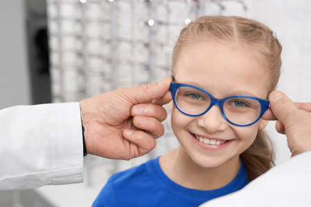Close up of child in blue glasses. Male doctor ophthalmologist helping pretty girl to choose eyeglasses. Doctor and patient in ophthalmology clinic. Concept of health care.