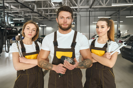 Pretty women and handsome man wearing in brown coveralls, white t shirts working as mechanics. Brutal muscular man and beautiful girls holding tools, looking at camera, posing.