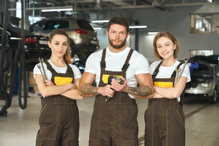 Three professional mechanics standing in autoservice, looking at camera. Beautiful women and brutal, muscular man with tattoos posing together, holding wrenches and tool. Imagens