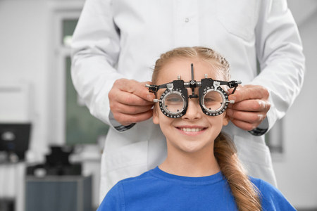 Ophthalmologist in white coat using special medical equipment for health of eyes, checking eyesight. Smiling girl sitting and looking at camera through test glasses.