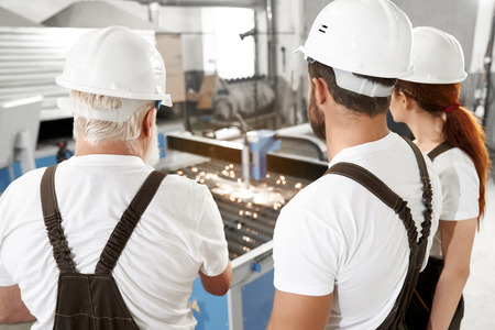 Back view of three engineers observing process of plasma laser cutting metal sheet with sparks. Workers wearing in white t shirts, white hardhats and coveralls. Imagens