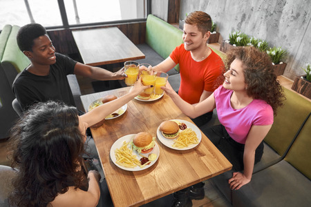 Group of friends sitting in cafe, talking, smiling and clinking glasses. Pretty girls and young men at wooden table with dishes of hamburgers, french fries and glasses of fresh orange juice.