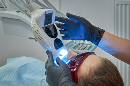 View from side of patient lying on dental chair during procedure of whitening of teeth. Woman wearing protective glasses while dentist keeping equipment radiating ultraviolet. Concept of beauty.
