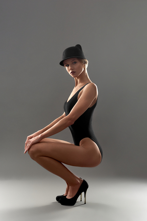 Beautiful lady in black body with hair picked up posing on grey background. Elegant model sportive body with long legs on high heel shoes sat down and leaned on his knees.