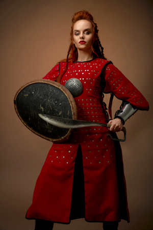 Brave, serious woman wearing as noble hero in red medieval tunic. Beautiful, charming model with ginger hair holding shield and dagger, posing in studio with weapon. Stock fotó