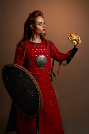 Beautiful woman warrior holding delicious hamburger in hand, looking at it. Serious, brave model wearing in medieval red dress, holding shield, standing and posing. 免版税图像