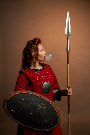 Brave female warrior wearing in red medieval costume blowing big bubble from chewing gum. Beautiful, gorgeous woman with red lips posing in studio, holding shield and big spear. Stock fotó