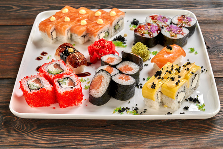 Different kinds of nigiri, maki and uramaki. Philadelphia, cheese uramaki, veggie rolls and nigiri served with wasabi and pickled ginger on white plate, wooden background. Stock Photo - 123026997