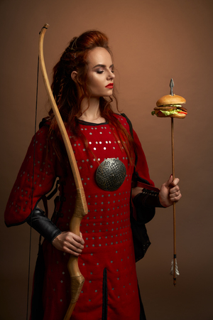 Medieval female warrior holding bow and arrow with hamburger, looking at tasty fast food burger. Gorgeous woman in red tunic with weapon posing and standing in studio.