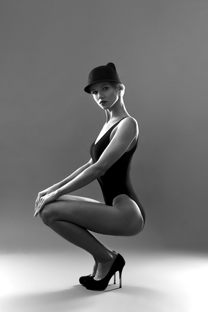 Fashionable model with sportive body, long legs on high heel shoes sat down and leaning on knees. Attractive lady in black body with hair picked up on grey background.