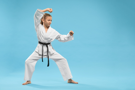 Side view of concentrated female child standing in karate stance in studio. Pretty teenager wearing white kimono looking at opponent and training on blue isolated background. Concept of judo.