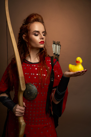 Beautiful woman warrior wearing in medieval red tunic holding small, yellow rubber duck on hand, looking at it. Serious model with red lips and ginger hair posing, holding bow.