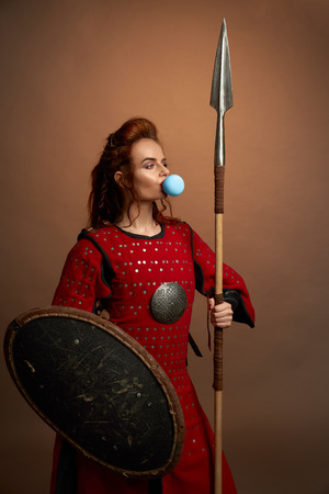 Female model looking away, blowing big blue bubble, chewing gum, holding spear and shield. Beautiful, brave woman with ginger hair standing, posing in studio, wearing in red medieval tunic. Stock fotó