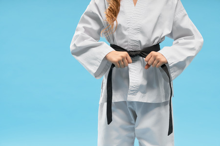 Front view of white kimono on little fighter keeping black belt on blue isolated background. Sporty child standing and posing in studio. Strong girl doing karate and judo. Concept of sport.