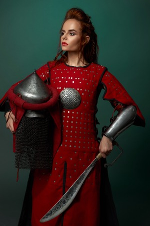 Gorgeous woman warrior holding medieval dagger and helmet, wearing in red medieval tunic. Beautiful woman with red lips and ginger hair posing in studio, looking away.