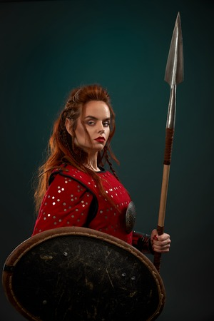 Brave female warrior wearing in red medieval costume looking at camera, holding shield and big spear. Beautiful, gorgeous woman with long ginger hair posing in studio with solid background. Imagens