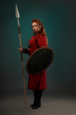 Brave female warrior with serious facial expression holding long spear and protective shield. Beautiful woman with ginger hair wearing in red medieval tunic, looking at camera, standing posing. Banque d'images - 122682730