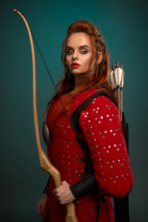 Gorgeous woman with ginger hair, red lips looking at camera, posing. Beautiful female warrior holding bow in hand, with arrows behind back, wearing in red medieval tunic.
