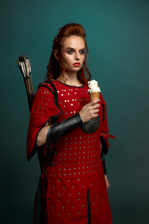 Gorgeous model with red lips and ginger hair posing, holding tasty, white ice cream. Beautiful woman warrior wearing in medieval red tunic with arrows behind back, looking away.