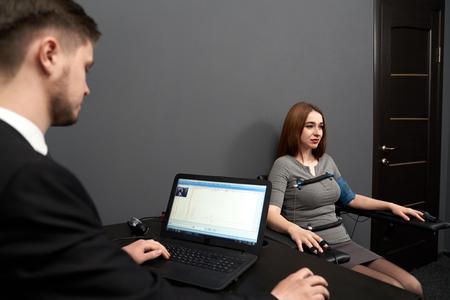 Konzentrierte Frau sitzt im grauen Raum und testet am Computerpolygraphen. Junger Mann, der am Tisch sitzt und Bildschirm des Polygraphen schaut und Polygraph überwacht. Standard-Bild