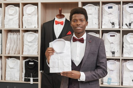 Young african man holding white shirt and posing in boutique of man clothing. Man in white shirt, red bow tie, waistcoat and grey jacket looking at camera. Shelves with shirts on background. Imagens - 122682224