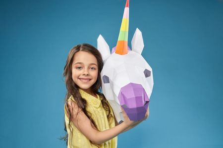 Portret of pretty, little, happy model with paper unicorn. Beautiful positive girl posing,looking at camera, smiling and holding hand on white 3D unicorn head. Papercraft concept.