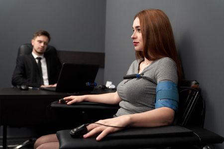 Beautiful, serious woman sitting in grey room and examinating on lie detector. Finger sensors, electrodes, wire on hands and body. Young man testing woman with computer polygraph.