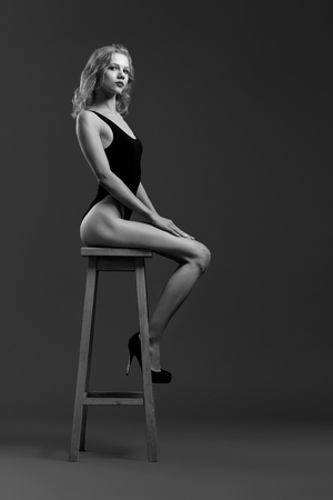 Beautiful girl with slender body, curly hair sitting on high chair. Gorgeous model in black underwear and high heel shoes posing and looking at camera. Black and white. Banco de Imagens - 122677764