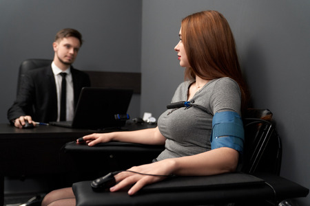 Woman sitting in chair with attached finger sensors and indicators, looking at lie detector. Young man at black table, testing woman with computer polygraph.