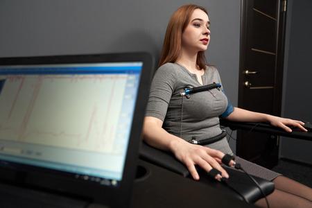 Giovane bella donna seduta con sensori attaccati su dita, mani e corpo, test con il poligrafo del computer, distogliendo lo sguardo. Grafico e poligrafo sullo schermo della macchina della verità.