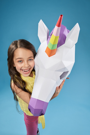 Creative papercraft. Beautiful little model posing with white 3D unicorn head on blue background. Positive, cute girl hugging paper unicorn. Portrait of girl and unicorn. 写真素材