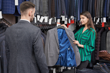Pretty shop consultant choosing, holding and showing grey jacket for young man. Man looking at big choice of suits and male clothing of fashionable prints on hangers in row.