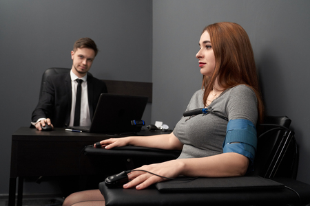 Frau sitzt im Stuhl mit angebrachten Fingersensoren und Draht und testet mit Lügendetektor. Junger Mann am Tisch mit Computerpolygraph, Überwachung von Lüge oder Wahrheit. Standard-Bild