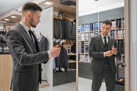 Handsome man in elegant striped suit standing, looking at mirror in boutique and choosing clothing. Young client in fashionable jacket, white shirt and black necktie. Imagens - 122679879
