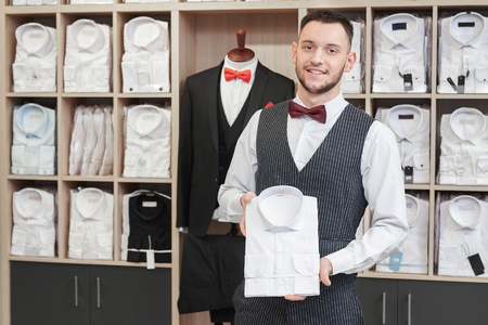 Portrait of young man, client of boutique on background with shirts on shelves. Confident man with beard holding white shirt, looking at camera, posing. Fashion boutique for men.