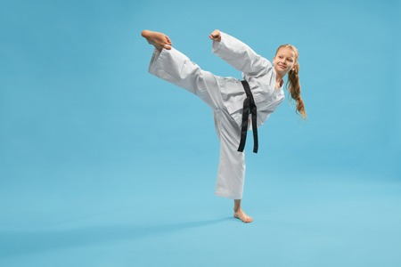 Active sporty girl wearing kimono kicking with leg on blue isolated background. Smiling female child doing taekwondo and practising jujitsu in studio. Concept of training process.