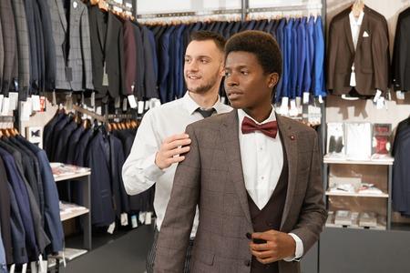 Assistente che aiuta e sceglie il vestito per l'uomo africano in un negozio alla moda. Cliente in camicia bianca, gilet, giacca e papillon rosso e venditore con barba in piedi al centro del negozio, guardando lontano. Archivio Fotografico