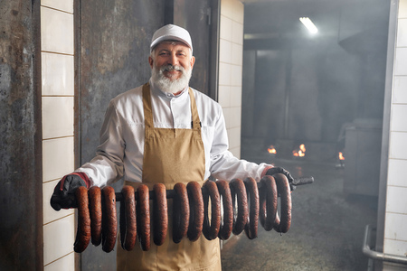 Smoked sassages hanging in row. Handsome smoker standing in smokehouse with smoked sausages, looking at camera. Elderly man wearing in white uhiform, brown apron, smiling, posing. 스톡 콘텐츠