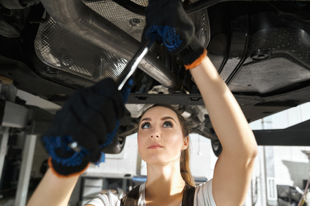 Close up of beautiful young woman fixing undercarriage of automobile. Concentrated girl in black gloves holding wrench, looking up on vehicle lifted on bridge. Autoservice station.